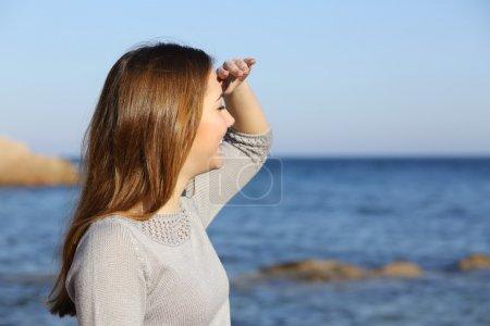 Photo pour Femme heureuse sur la plage d'impatience à l'horizon de sa main au front - image libre de droit