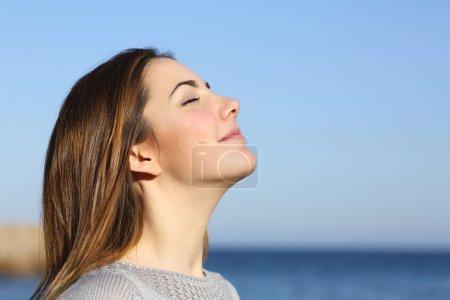 Photo pour Portrait de femme respirant l'air frais profond sur la plage avec l'océan en arrière-plan - image libre de droit