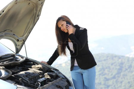 Photo for Woman on the phone looking her crash breakdown car in a road in the middle of the mountain - Royalty Free Image