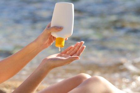 Photo pour Femme mains mettre un écran solaire d'une bouteille sur la plage avec la mer en arrière-plan - image libre de droit