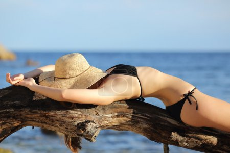 Fitness woman sunbathing on the beach sleeping