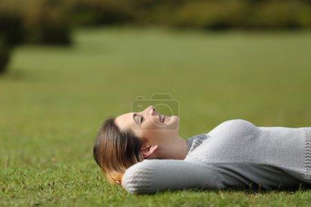 Photo pour Belle femme reposant sur l'herbe dans un parc ou à la montagne avec un arrière-plan flou - image libre de droit
