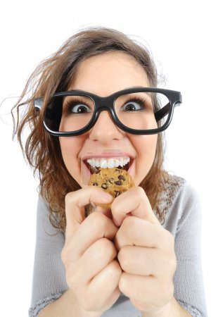 Photo for Funny geek girl eating a cookie isolated on a white background - Royalty Free Image