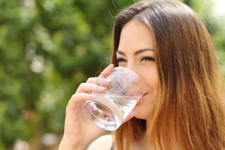Photo for Happy healthy woman drinking fresh water from a glass outdoor with a green background - Royalty Free Image