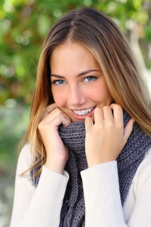 Photo for Beautiful woman with a white perfect smile and blue eyes in winter warmly clothed - Royalty Free Image