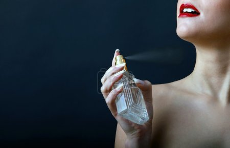 Photo pour Souriant vaporisateur le parfum d'une bouteille de la fille - image libre de droit