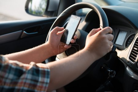Photo for Texting and talking while driving, hands of young man on steering wheel - Royalty Free Image