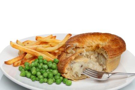 Foto de Chips de pastel de pollo y guisantes en un plato con un tenedor - Imagen libre de derechos