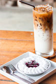 Blueberries cheesecake serving with iced coffee latte