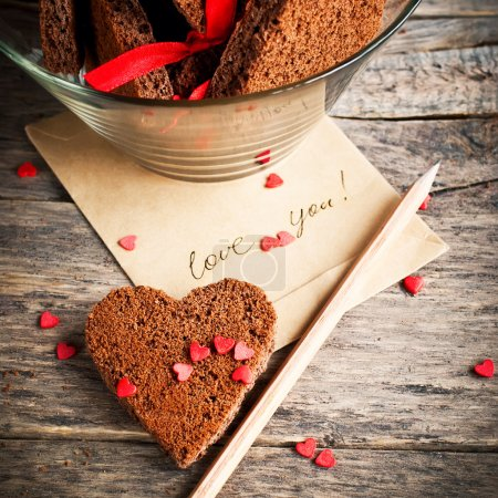 Photo for Card with Message Love You in the Letter and Chocolate Cookies in the Shape of Heart at Valentine Day - Royalty Free Image