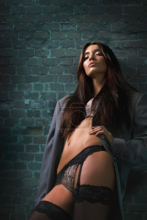 Attractive brunette in sexy lingerie and men's jacket leaning on