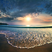 Summer sea design template. Beautiful sunset on tropical beach with shorebreak and sunlight on horizon