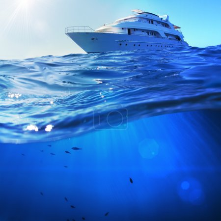 beautiful sunlight seaview safari dive boat in tropical sea with deep blue underneath splitted by waterline