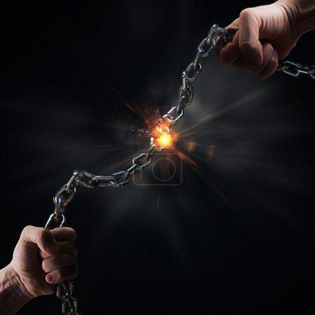 Man tearing heavy steel chain