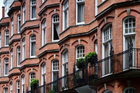 Photo pour Une rangée de briques rouges abrite avec menuiseries blanches. Situé en bas de la rue près de piccadilly, Londres, Royaume-Uni. - image libre de droit
