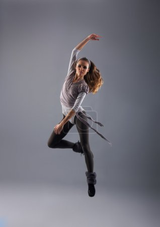 Young, attractive, sporty and sexy modern dancer jumping over grey background