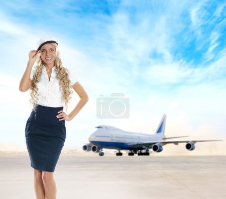 Sexy stewardess over background of airport and plane