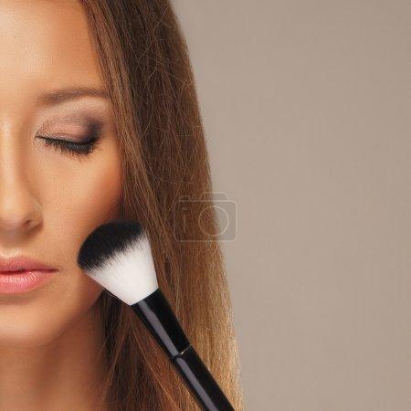 Photo pour Photo Studio du processus de maquillage sur fond gris - image libre de droit