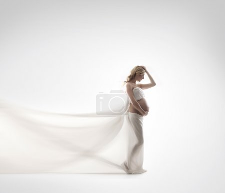 Young and beautiful pregnant woman in antique dress