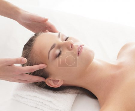 Young attractive woman getting massaging treatment over white ba