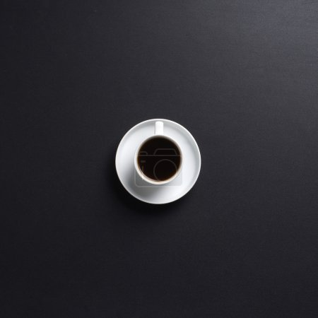 Cup of coffee over the black background