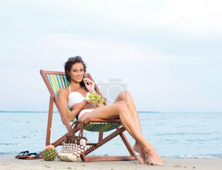 Sexy woman eating grapes on the beach
