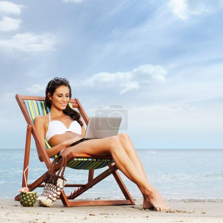 Photo for Young, beautiful, sporty and sexy woman with the notebook pc relaxing on the beach - Royalty Free Image