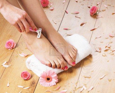 Photo pour Femme rasant ses jambes sur le fond du spa - image libre de droit