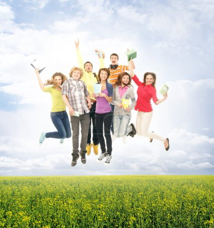 Photo for Group of smiling teenagers jumping together and looking at camera over the summer background - Royalty Free Image