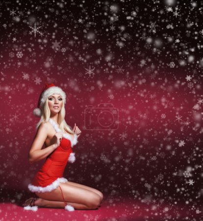 Photo for Young, sexy and beautiful female Santa over Christmas background with snowflakes - Royalty Free Image