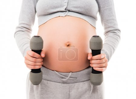 A pregnant woman working out with dumbbells