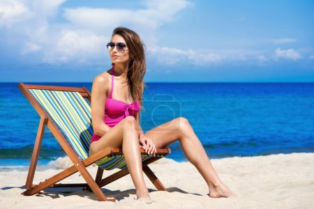 A young brunette woman in a white swimsuit relaxing on the beach