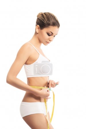 A young and fit woman with a measuring tape