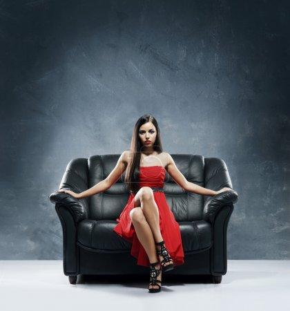 Photo pour Jeune, belle et femme glamour en robe rouge assis sur le canapé en cuir noir - image libre de droit