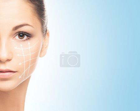Photo pour Gros plan portrait d'une jeune femme belle et en bonne santé avec des flèches sur le visage (spa, chirurgie, lifting du visage et concept de maquillage) ) - image libre de droit