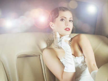 Photo for Young and beautiful celebrity woman sitting in a luxury car - Royalty Free Image