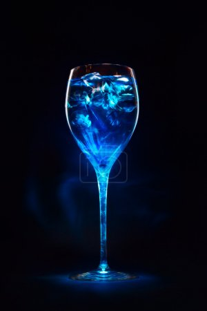 Photo for Amazing blue cocktail with ice cubes in high glass. Blue curacao liquor. Magic lights and shadows. - Royalty Free Image
