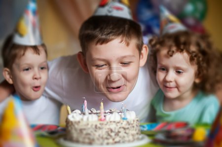 Boy blows out the candles on a birthday cake and hugs his brothe