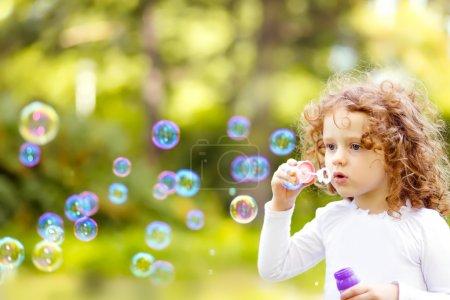 Photo pour Une petite fille soufflant des bulles de savon, gros plan portrait beau bébé bouclé . - image libre de droit