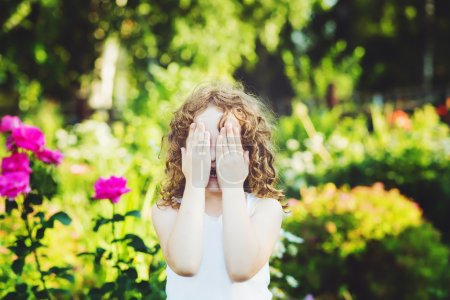 Little girl closed face with her hands, weeping, or playing hide