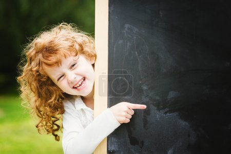Back to school. Girl at blackboard. Educational concept. Place f