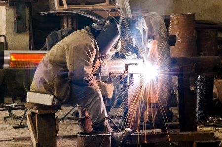 Photo pour Étincelles et gouttes de métal fondu pendant le travail du soudeur . - image libre de droit