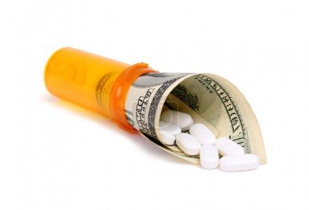 Bottle of pills and money isolater on white