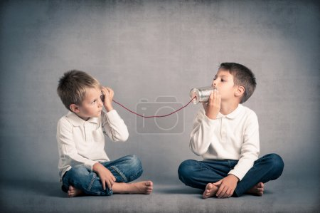 Young brothers talking with tin can telephone on grunge background