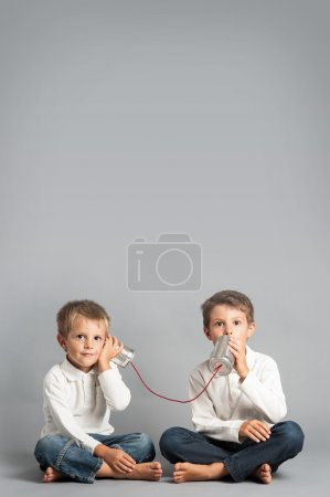 Photo for Young brothers talking with tin can telephone. - Royalty Free Image