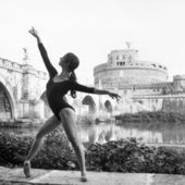 Young beautiful ballerina dancing out in Tevere riverside with castel Santangelo in the background in Rome, Italy. Black and white image. Ballerina Project.