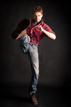 Photo pour Jeune homme coup de pied sur fond noir - image libre de droit