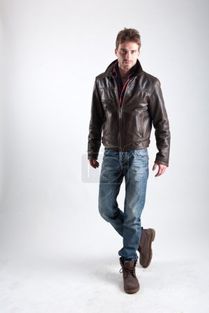 Portrait of young man with leather jacket against white background