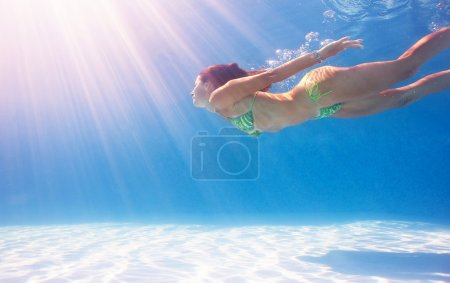 Woman swimming underwater in a blue pool