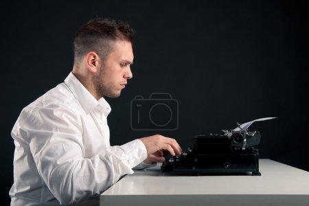 Photo pour Jeune homme écrit avec une vieille machine à écrire. image rétro - image libre de droit